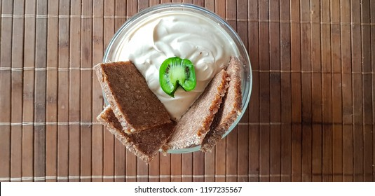 Healthy protein breakfast, quark dip, flax seed oil with omega 3, fresh fruits and rustic wholemeal bread with tomatoes on a kitchen board, healthy and concentrated meal with natural food