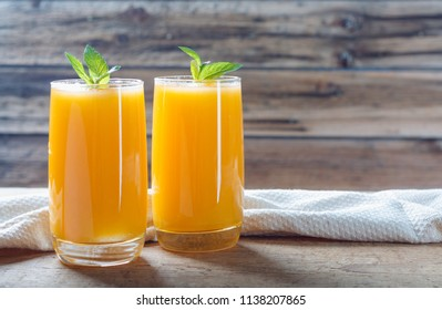 Healthy pumpkin fruit smoothie  mint leaves on old wooden table.