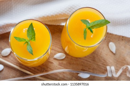 Healthy pumpkin fruit smoothie with seeds and mint leaves on old wooden table. Top view flat lay group objects