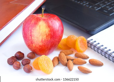Healthy quick snack (lunch) in office. Red apple, dry fruits (apricots) and nuts on desk with computer and planner.