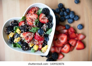 Healthy quinoa fruit salad in heart shaped bowl, flat lay.