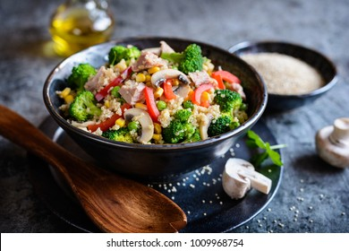 Healthy quinoa salad with tuna, broccoli, peas, bell pepper, corn and mushrooms