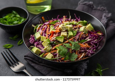 healthy rainbow cole slow, red cabbage, avocado, carrot and bell pepper salad in black bowl, selective focus