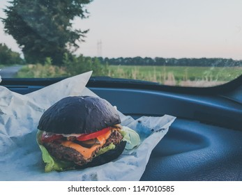 Healthy raw black bun burger with cheese, tomato, lettuce and bacon on car dash against the evening sky background.Close up, shallow depth of the field, toned and processing photo.