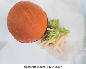 Healthy raw bun burger with chees, tomato, lettuce and bacon on wooden table in cafe.Close up, shallow depth of the field, toned and processing photo.