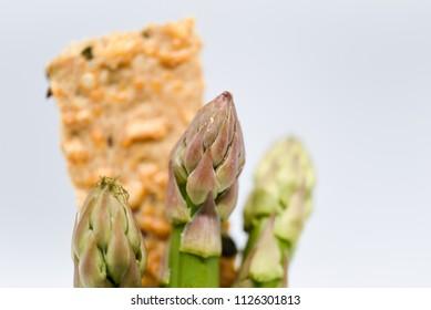 healthy raw fresh vegetarian vegan mic close up macro whole grain cracker bread and fresh green asparagus diet concept