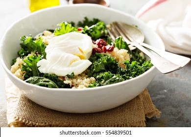 Healthy raw kale and quinoa salad with poached egg on top
