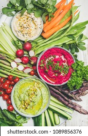 Healthy raw summer vegan snack plate. Flat-lay of Chickpea, beetroot, spinach hummus dips with fresh vegetables and greens on white background, top view. Clean eating, dieting, vegetarian party food