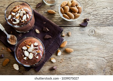 Healthy Raw Vegan Chocolate Mousse topped with Almond in glasses over wooden background close up - delicious homemade Raw Vegan Chocolate Pudding with Nuts and Carob powder