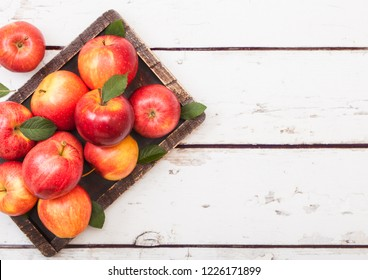Healthy red organic  apples in vintage box on wood background.