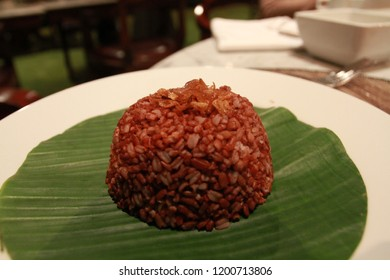 Healthy red rice on the white plate and fresh green banana leaf serve to the guest in Sasanti restaurant