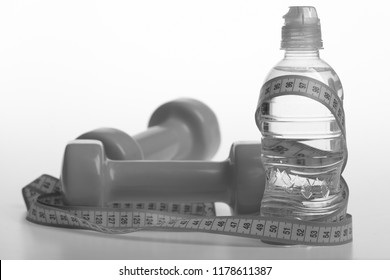 Healthy regime equipment. Athletics and weightloss concept. Water bottle tied with cyan measure tape by green dumbbells on white background. Bottle wrapped with turquoise ruler by lightweight barbells