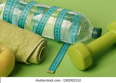 Healthy regime equipment. Barbell made of plastic by juicy green apple. Diet and sport regime concept. Dumbbell in bright green color, water bottle, measure tape, towel and fruit on green background