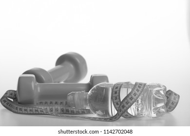Healthy regime equipment. Water bottle tied with cyan measure tape by green dumbbells on white background, copy space. Diet and sport regime concept. Bottle wrapped with ruler by lightweight barbells.