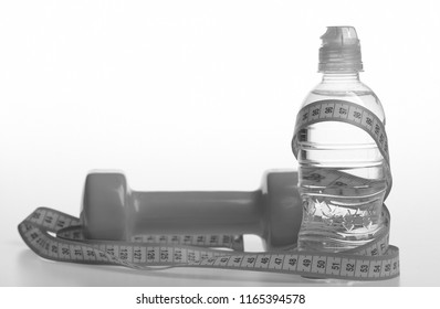 Healthy regime equipment. Water bottle tied with cyan measure tape by green dumbbell on white background, copy space. Diet and sport regime concept. Bottle wrapped with ruler by lightweight barbell