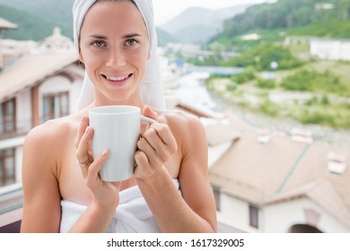 Healthy relaxed young woman in bath towels drinks wellness herbal tea while standing on the balcony of her hotel room during a wellness trip. Health and beauty spa concept