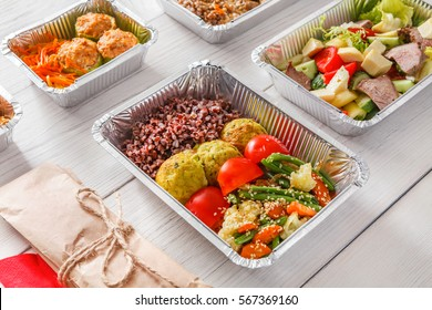 Healthy restaurant food. Chef prepared diet daily meals delivery. Fitness nutrition, vegetables, meat and fruits in foil boxes, cutlery in craft package on wood
