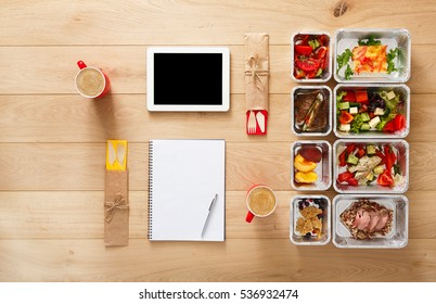 Healthy restaurant food for couple and diet plan. Fresh daily meals delivery. Fitness nutrition, vegetable, meat and fruits in foil boxes, coffee and tablet. Top view, flat lay on wood with copy space