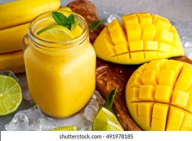 Healthy ripe Yellow Banana Mango Smoothie with slices of Lime, mint and ice. concept healthy food