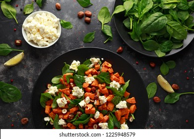 Healthy roasted sweet potato salad with spinach, feta cheese, hazelnut nuts in black plate.