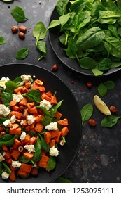 Healthy roasted sweet potato salad with spinach, feta cheese, hazelnut nuts in black plate