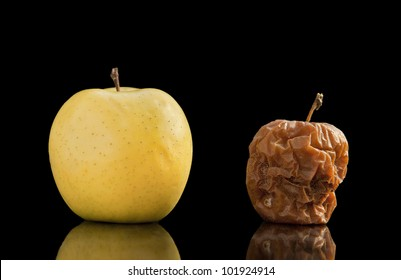 Healthy and rotten yellow apple isolated on black with reflection.