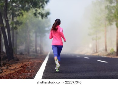 Healthy running runner woman workout on mountain road. Jogging female fitness girl working out training for marathon on forest road in amazing nature.