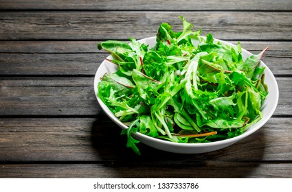Healthy salad. Arugula salad in a bowl. On a wooden background.