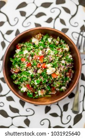 Healthy salad bowl from above. This healthy dish mixes tabbouleh & greek style salads, using fresh parsley herb, olives, onions, feta and replacing the bulgur usually found in tabouleh with quinoa.