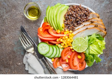 Healthy salad bowl with quinoa, tomato turkey, avocado, sweet pepper, corn, lime and mixed greens, top view. Healthy food conception. Superfood meal.