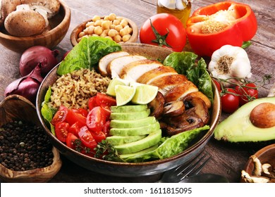 Healthy salad bowl with quinoa, tomatoes, chicken, avocado, lime and mixed greens, lettuce. Food and health.