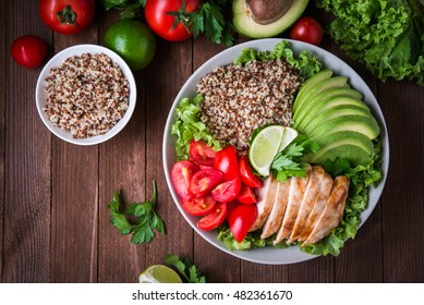 Healthy salad bowl with quinoa, tomatoes, chicken, avocado, lime and mixed greens (lettuce, parsley) on wooden background top view. Food and health. Superfoods.