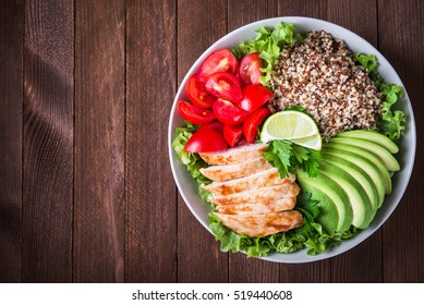 Healthy salad bowl with quinoa, tomatoes, chicken, avocado, lime and mixed greens, lettuce, parsley on wooden background top view. Food and health. Space for text.