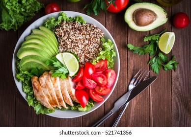 Terveellinen salaattikulho, jossa quinoa, tomaattia, kanaa, avokadoa, kalkkia ja sekoitettuja vihreitä, salaattia, persiljaa puisella taustalla ylhäältä. Ruoka ja terveys.