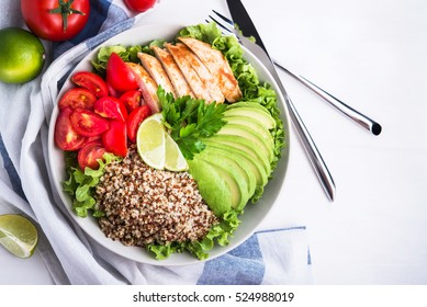 Healthy salad bowl with quinoa, tomatoes, chicken, avocado, lime and mixed greens, lettuce, parsley, on white wood background top view. Food and health. Superfoods meal.