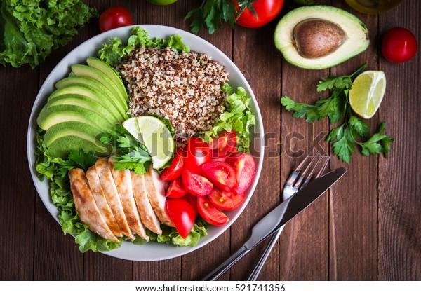 Sano plato de ensalada con quinua, tomates, pollo, aguacate, lima y verduras mezcladas, lechuga, perejil en la parte superior de madera. Alimentos y salud.