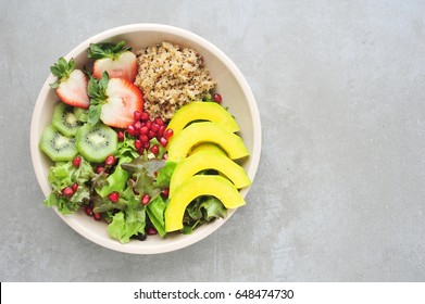Healthy salad bowl with quinoa,avocado,lettuce on cement background top view.Healthy food.
