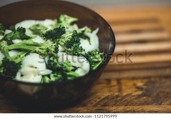 Healthy salad with broccoli, eggs, onion and green salad.