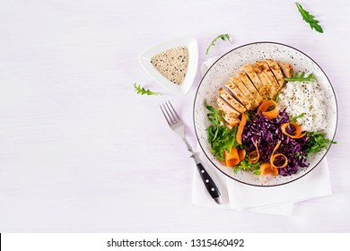 Healthy salad. Buddha bowl dish with chicken fillet, rice,  red cabbage, carrot, fresh lettuce salad and sesame. Healthy balanced eating. Top view.