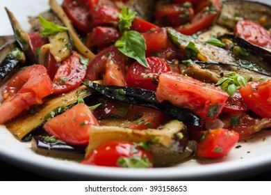 Healthy salad with cherry tomatoes, eggplant, fresh greens in white plate close up macro