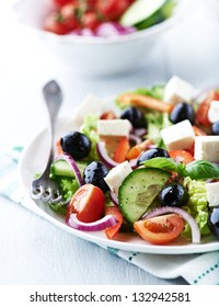 Healthy salad with cherry tomatoes, feta cheese, cucumber, black olives, red onion, lettuce, spices and fresh basil. Greek salad. Concept for healthy nutrition. Bright wooden background. Close up.