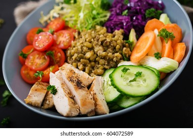 Healthy salad with chicken, tomatoes,  cucumber, lettuce, carrot, celery, red cabbage and  mung bean on dark background. Proper nutrition. Dietary menu.