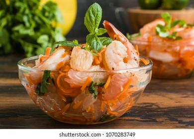 Healthy salad with fried shrimps, fresh carrot, pomelo, coriander and mint in glass bowls on wooden rustic table, close-up
