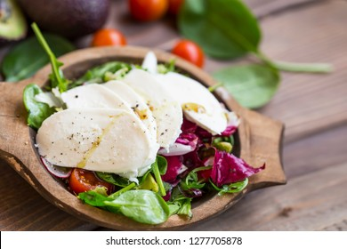Healthy salad with green leaves, red cabbage, tomatoes, radish and mozarella cheese slices in woden bowl