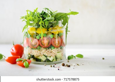 Healthy salad jar with quinoa and vegetables, cherry tomatoes, cucumber, ruccola. Raw vegetarian meal for diet, detox, clean eating. Homemade concept.