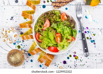 Healthy salad and measuring tape on Christmas holidays background. Before or after holidays diet and sport concept