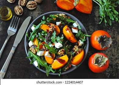 Healthy salad with persimmon, arugula, nuts and feta cheese. Fitness food. Superfoods Vitamin autumn persimmon salad.