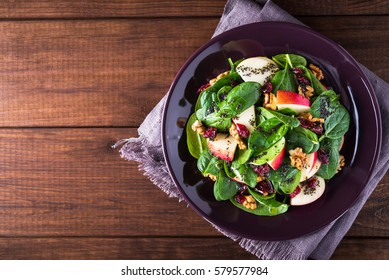 Healthy salad plate with apple, dried cranberry, walnut, spinach and poppy seed dressing on wooden background top view. Healthy food. Clean eating.