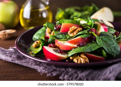 Healthy salad plate with apple, dried cranberry, walnut, spinach and poppy seed dressing on wooden background close up. Healthy food. Clean eating.