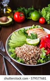 Healthy salad plate with quinoa, cherry tomatoes, chicken, avocado, lime and mixed greens, lettuce, parsley on wooden background close up. Food and health. Superfood meal.